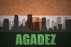Abstraktes Schattenbild der Stadt mit Text Agadez an der Weinleseniger-Flagge Stockbild