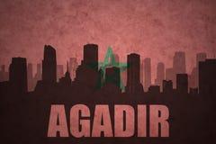 Abstraktes Schattenbild der Stadt mit Text Agadir an der Weinlesemarokkanerflagge Stockfotografie