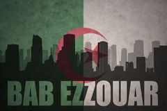 Abstraktes Schattenbild der Stadt mit Text Bab Ezzouar an der Weinlesealgerierflagge Lizenzfreies Stockfoto