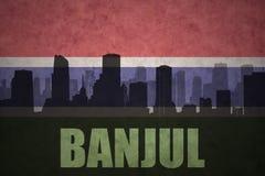 Abstraktes Schattenbild der Stadt mit Text Banjul an der Weinlesegambia-Flagge Lizenzfreie Stockfotos