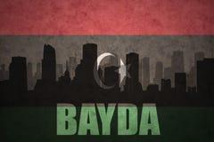 Abstraktes Schattenbild der Stadt mit Text Bayda an der Weinleselibyerflagge Stockfotografie