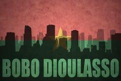 Abstraktes Schattenbild der Stadt mit Text Bobo Dioulasso an der Weinleseburkina faso Flagge Stockfotografie