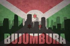 Abstraktes Schattenbild der Stadt mit Text Bujumbura an der Weinleseburundi-Flagge Stockfotos