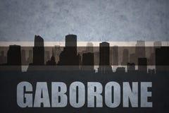 Abstraktes Schattenbild der Stadt mit Text Gaborone an der Weinlesebotswana-Flagge Stockfoto