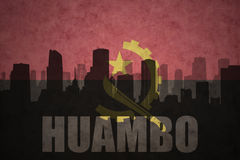 Abstraktes Schattenbild der Stadt mit Text Huambo an der angolanischen Flagge der Weinlese Stockfotografie