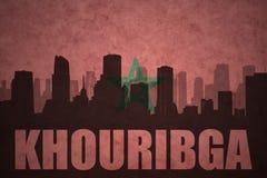 Abstraktes Schattenbild der Stadt mit Text Khouribga an der Weinlesemarokkanerflagge Lizenzfreie Stockbilder
