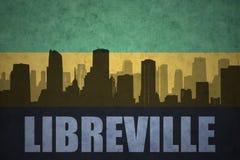 Abstraktes Schattenbild der Stadt mit Text Libreville an der Weinlesegabonese-Flagge Lizenzfreie Stockfotografie