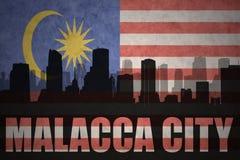Abstraktes Schattenbild der Stadt mit Text Malakka-Stadt an der malaysischen Flagge der Weinlese Lizenzfreies Stockfoto