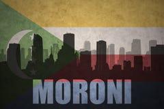 Abstraktes Schattenbild der Stadt mit Text Moroni an der Weinlesecomoren-Flagge Stockfotografie