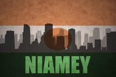 Abstraktes Schattenbild der Stadt mit Text Niamey an der Weinleseniger-Flagge Stockfotografie