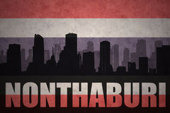 Abstraktes Schattenbild der Stadt mit Text Nonthaburi an der Weinlesethailand-Flagge Stockfoto