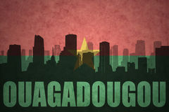 Abstraktes Schattenbild der Stadt mit Text Ouagadougou an der Weinleseburkina faso Flagge Lizenzfreie Stockfotos