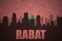 Abstraktes Schattenbild der Stadt mit Text Rabat an der Weinlesemarokkanerflagge Lizenzfreie Stockfotos