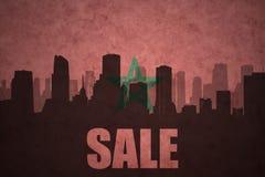 Abstraktes Schattenbild der Stadt mit Text Verkauf an der Weinlesemarokkanerflagge Lizenzfreie Stockfotografie