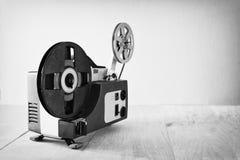 Abstraktes Schwarzweiss-Bild des alten 8mm Film-Projektors über Holztisch und strukturiertem Hintergrund Stockfotografie