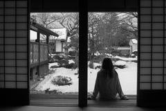 Abstraktes Schwarzweiss-Bild des einsamen Frauensitzens entspannen sich auf hölzerner Terrasse und vorwärts schauen zum japanisch stockfoto