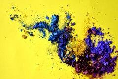 Abstraktes Spritzen des blauen und purpurroten Pulvers auf gelbem Hintergrund stockfoto