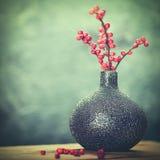 Abstraktes Stillleben mit keramischem Vase und roten Beeren Stockfotos