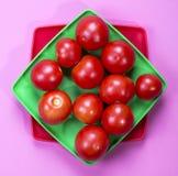 Abstraktes Stillleben mit Tomaten auf einer grünen Platte Stockfotografie