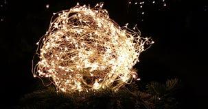 Abstraktes Weihnachtsfunkeln beleuchtet Ball auf Weihnachtsbaum mit warmem Schein bokeh auf schwarzem Hintergrund, Konzept golden stock footage