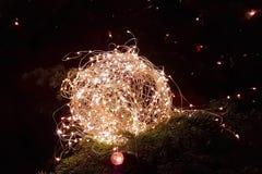 Abstraktes Weihnachtsfunkeln beleuchtet Ball auf Weihnachtsbaum mit warmem SP Stockbilder