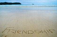 Abstraktes Zeichen der Wortfreundschaft geschrieben auf einen Sandstrandhintergrund Lizenzfreies Stockfoto
