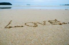 Abstraktes Zeichen der Wortliebe geschrieben auf einen Sandstrandhintergrund Lizenzfreie Stockfotos
