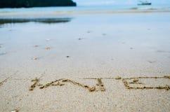 Abstraktes Zeichen des Worthasses geschrieben auf einen Sandstrandhintergrund Lizenzfreie Stockfotografie