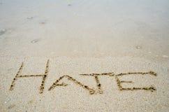 Abstraktes Zeichen des Worthasses geschrieben auf einen Sandstrandhintergrund Stockfotografie