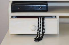 Abstraktion auf schwarzen Perlen einer Frisierkommode und einem Fotoalbum Stockbilder