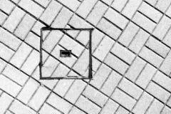 Abstraktion des Abwasserkanaleinsteigelochs auf Boden mit Kopfsteinen Stockfotografie