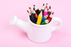 Abstraktion von den Gartenwerkzeugen und von farbigen Bleistiften Lizenzfreie Stockfotografie