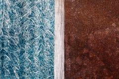 Abstraktionen av blå textolite kritiserar, bakgrund i halva med en rostig metallplatta och en delande remsa av trä royaltyfri foto