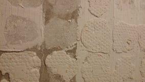Abstreifende Fliesen auf einer Wand - im Bau Stockbild