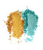 Abstriche der zerquetschten Knickente und des goldenen glänzenden Lidschattens als Probe von Kosmetik Lizenzfreie Stockfotografie
