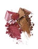 Abstriche von zwei zerquetschten braunen und purpurroten glänzenden Lidschatten als Probe des kosmetischen Produktes Stockbilder