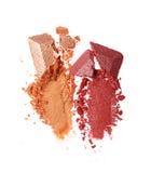 Abstriche von zwei zerquetschten glänzenden beige und roten Lidschatten als Probe des kosmetischen Produktes Stockbild