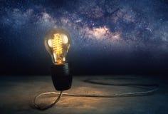 abstrract helle Glühlampe, die mit Milchstraßehintergrund steht, Stockfotografie
