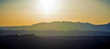 Abstufungen der Berge unter dem aufgehende Sonne Stockfoto