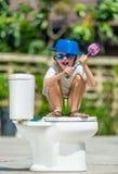 Absurd beeld: leuke jongen die in beschermende brillen op het toilet zitten, dat stock fotografie