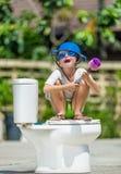 Absurd beeld: leuke jongen die in beschermende brillen op het toilet zitten, dat royalty-vrije stock afbeeldingen