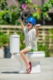 Absurdes Bild: nettes Jungentanzen auf der Toilette, die mitten in der Straße installiert ist Pan auf seinem Kopf Stockfotografie