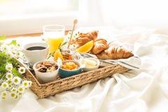 Abtropfbrett mit kontinentalem Frühstück auf weißen Bettlaken Lizenzfreies Stockfoto