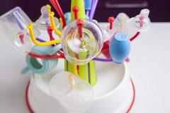 Abtropfgestell voll von Babyplastikgeschirrgegenständen Stockfotos