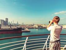 Abu Dhabi, Arabische Emirate - 13. Dezember 2018: Junger Mann, der durch Ferngläser von einem Kreuzfahrtschiff zu einer Stadt auf stockfotografie