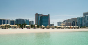 Abu Dhabi Beach. With sun umbrellas with skyline on the background viewed from the sea royalty free stock image