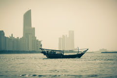 Abu Dhabi buildings skyline. With old fishing boat on the front Royalty Free Stock Image