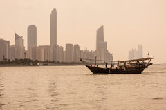 Abu Dhabi buildings skyline. With old fishing boat on the front Royalty Free Stock Photo