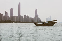Abu Dhabi buildings skyline with old fishing boat. On the front Royalty Free Stock Photo