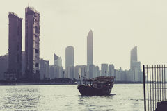 Abu Dhabi buildings skyline with old fishing boat Stock Image